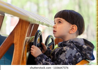 One cute boy on carousel ride in vintage car in children's park.