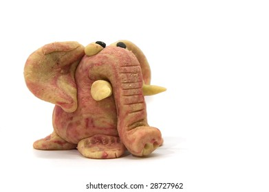 One cute, home-made pink elephant, made from colored marzipan, on white