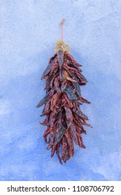 One decorative bunch of dried red chilis hanging on a blue stucco wall