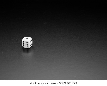 One die isolated on dark gradient background