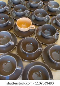 One different colored coffee cup stands alone in a group of identical brown cups and saucers on a table.