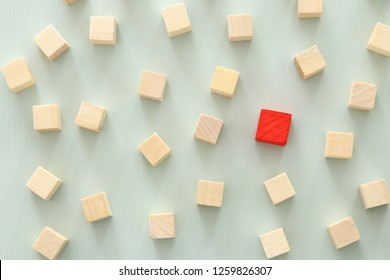 One different red cube block among wooden blocks. Individuality, leadership and uniqueness concept