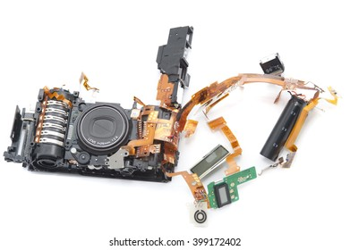 One disassembled digital camera with exposed lens and green soldered board against a white background