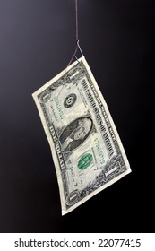 One dollar banknote on a fish-hook. Decoy concept. Gray-black backdrop.