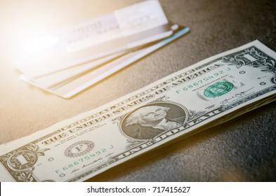 One dollar banknotes on a black table with credit cards. Cash money american dollars. Vintage background. Lens flare. American currency. Internet banking