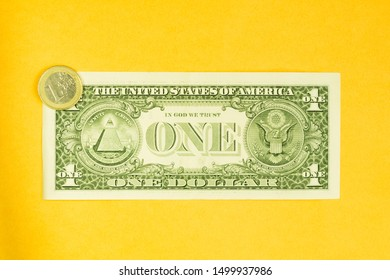 One dollar bill and one euro coin isolated on yellow background. coin lies on a banknote