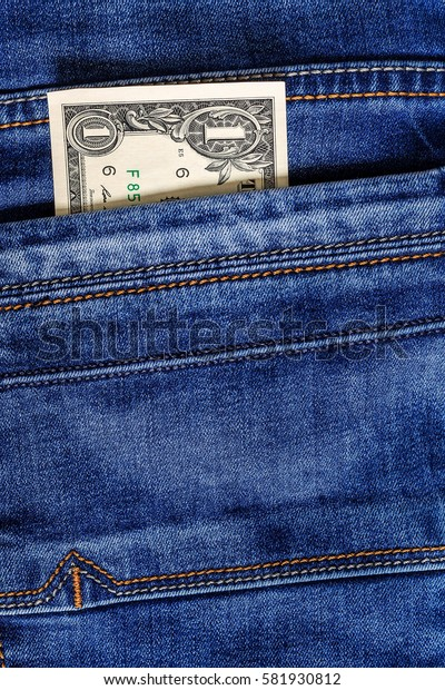 One dollar bill in the pocket of  blue jeans. Cash money.