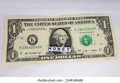 One dollar bill with the word money in letters. Image of the dollar bills in vertical on white background