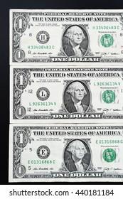One dollar bills on black background