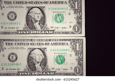 One dollar bills on black background