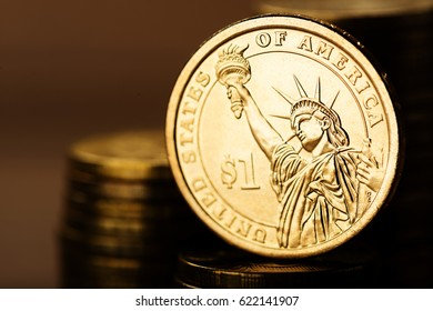 One dollar coin and gold money on the desk
