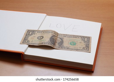 One dollar with love on a book on wooden table