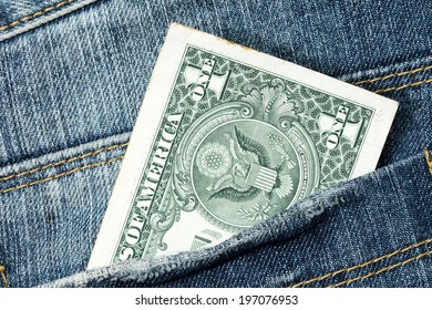 One dollar note in the back pocket of denim trousers