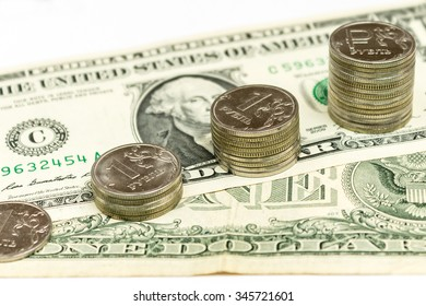 one dollar and one ruble, the columns of coin in one ruble on the background of banknotes of one dollar