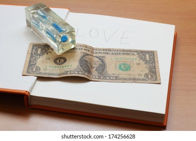 One dollar and sandglass with love on a book on wooden table