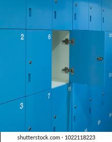 one door of blue locker opened in swimming bathroom