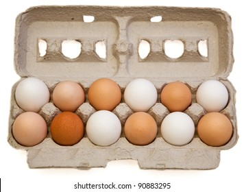 A one dozen carton of free range organic eggs from various chickens in different colors and sizes isolated on a white background.