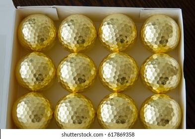 One dozen gold leafed golf balls in a box