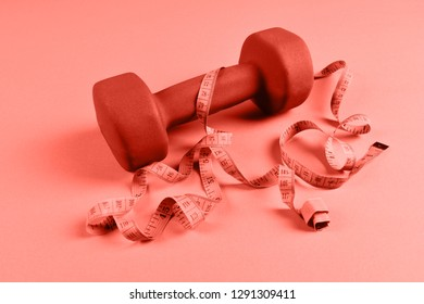One dumbbell and measuring tape toned in coral color which is the main trend of 2019.