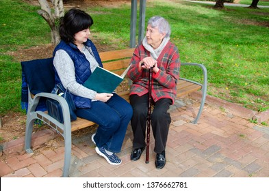 One of the duties of this female caregiver is daily reading for an elderly woman. During a walk in the park, they sit on a bench and the carer reads a book. The old lady listens attentively.