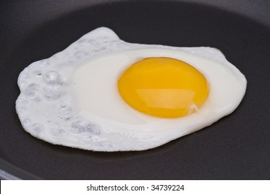 One egg in a black skillet frying pan