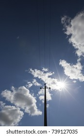 one electric pole with metal wires against a blue sky and a bright glowing sun. photo close-up, bottom view