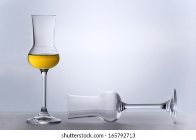 One empty Grappa glass lying and one filled standing