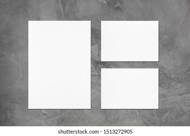 One empty white vertical a4 sized poster and two a5 sized horizontal rectangle card mockups with soft shadows on dark grey concrete background. Flat lay, top view