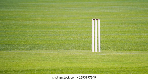 One end of a cricket pitch showing a set of stumps