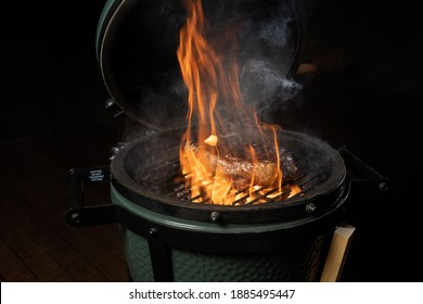 One enveloped in flame new york steak in an egg type grill.