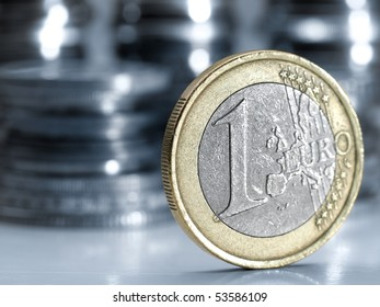 One euro money coin , closeup with stacks of coins in the background, shallow DOF , blue toned image