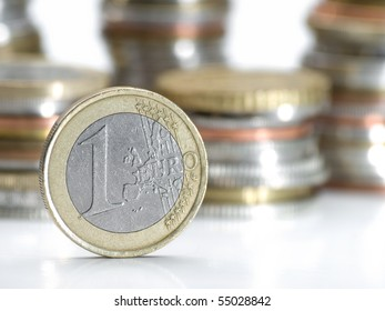 One euro money coin , closeup with stacks of coins in the background, shallow DOF, useful for various economy or financial themes