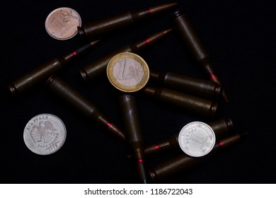 One euro, one Russian ruble and Ukrainian hryvna coins with rifle military ammo on black background. Symbolizes war for money- biggest problem in world.
