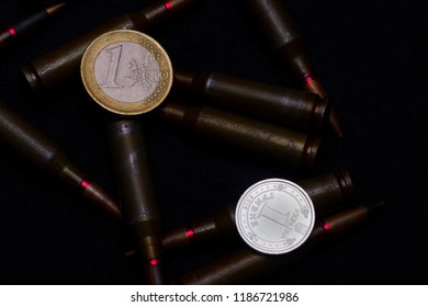 One euro and Ukrainian hryvna coins with rifle military ammo on black background. Symbolizes war for money- biggest problem in world.