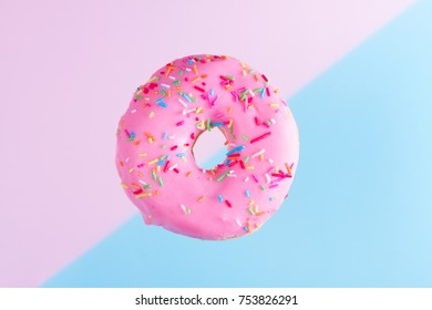 one falling sweet doughnut on blue and pink abstract background with copy space