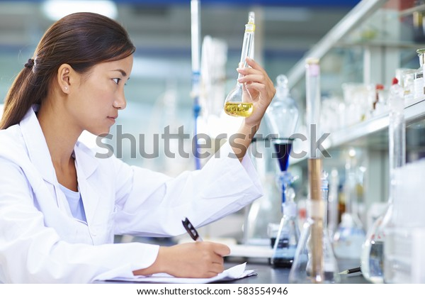 One Female Chinese Laboratory scientist working at lab with test tubes