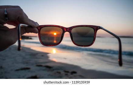 One female hand holding a pair of sunglasses, showing the view of a beautiful sunset and beach. Taken along the Wild Atlantic Way in County Galway, Ireland