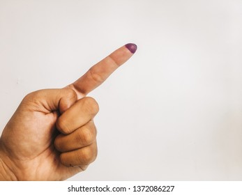 One finger or index finger of hands of a man who is isolated on a white background. Purple ink spots from the voters' fingers gave evidence of Indonesian elections. Sign for Jokowi supporter.