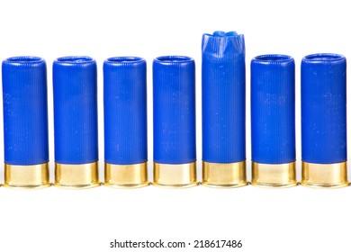 One fired shotgun shell among unused ammo isolated on white