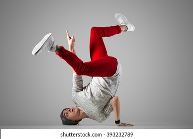 One fit young man in casual red jeans working out, performing breakdance moves on the floor. Full length photo on studio gray background