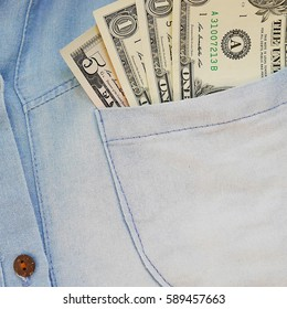 One and five dollar money banknotes in a light denim shirt pocket. Money in daily life of people in USA and around the World. Personal financial concept.