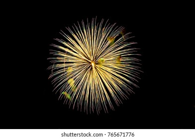 One flash of yellow salute fireworks on a black sky