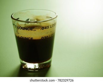 One fluid ounce of rich black coffee or espresso in shot glass on pastel green background with beautiful sunspot. (close up, selective focus, toned, space for text)