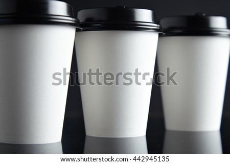 1cd394c4626 One focused paper cup for hot drinks between two unfocused presented on black  back and mirrored