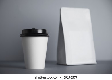 One focused take away white paper cup with black cap presented near blank white bag, isolated on of simple gray background