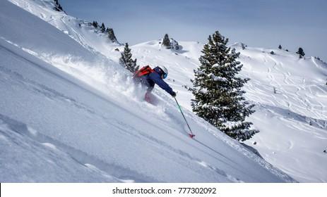 One freeride skier charging downhill through fresh and deep snow, Kuhtai Austria