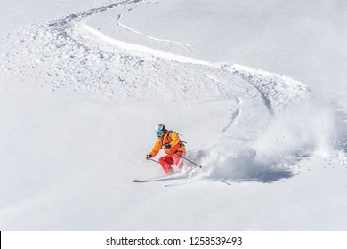 one freeride skier skiing downhill trough deep fresh powder