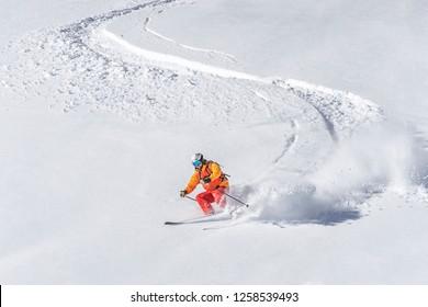 one freeride skier skiing downhill trough deep fresh powder