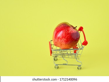 One fresh apple in Small shopping trolley closeup with on a yellow background. The concept of home delivery, online shopping, clearance sale.healthy food. food donatio