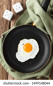 One fresh fried egg sunny side up in skillet, salt and pepper shaker on the side, photographed overhead (Selective Focus, Focus on the egg)